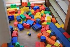 Hög av färgrika stora kvarter som bygger leksakerskum Förskole- inomhus lekplats för utbildning royaltyfri bild