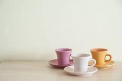 Hög av färgrika tappningkoppar kaffe på trätabellen royaltyfri fotografi
