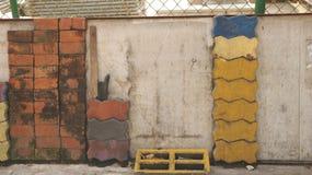 Hög av färgrika tegelstenar vid den gamla väggen för tappning med försett med en hulling - trådstaket arkivfoton