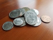 Hög av fjärdedelen för USA-valutafrihet och andra mynt på trätabellen royaltyfria foton