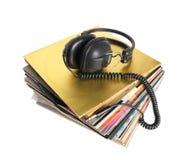 Hög av gamla isolerade vinylrekord och tappninghörlurar Arkivbilder