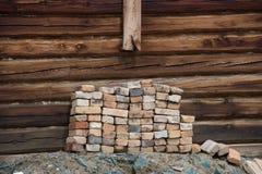 Hög av gamla tegelstenar på bakgrundsväggen ett trähus Royaltyfri Bild