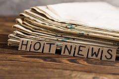 Hög av gamla tidningar bredvid papprektangelfyrkanter med varm nyheterna för handskriven inskrift på den gamla bruna trätabellen arkivbild