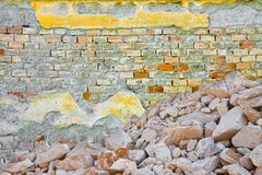 Hög av grus, stenar och kiselstenar av olika format mot en skadad tegelstenvägg royaltyfri bild