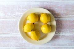 Hög av gula citroner på en platta Royaltyfri Fotografi