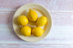 Hög av gula citroner på en platta Arkivfoto