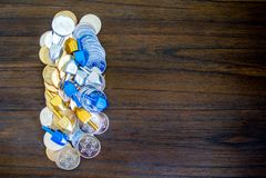 Hög av guld- och silverChanukkahmynt med mycket små dreidels royaltyfria bilder