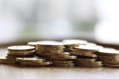 Hög av guld- pengarmynt på vit bakgrund för kopieringstext arkivbild