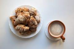 Hög av hemlagade giffel och koppen av varm latte från över arkivbilder
