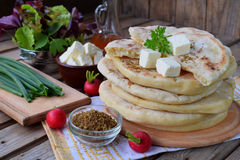 Hög av hemlagat plant bröd med grönsallat, ost, löken och rädisan på en träbakgrund Mexicansk tunnbrödtaco Indier Naan Arkivfoton