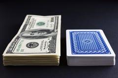 Kortlek och hög av pengar Arkivbild
