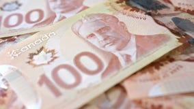 Hög av hundra dollarsedlar på en tabell arkivbild