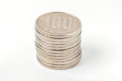 Hög av japanska pengar för 100 yenmynt på vit bakgrund Arkivbilder