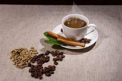 Hög av java bönor och örter med varmt kaffe Arkivbilder