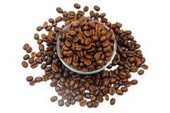 Hög av kaffebönor runt om och inom den glass bunken Royaltyfria Bilder