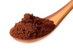 Hög av kakao i träsked på vit Royaltyfri Foto