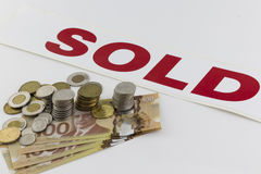 Hög av kanadensiska pengar med det sålda tecknet fotografering för bildbyråer