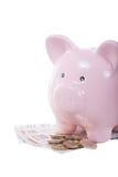 Hög av kontanta pengar med en rosa spargris arkivbilder