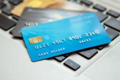 Hög av kreditkortar på bärbar datortangentbordet Öppet tillträde för online-shopping arkivfoto