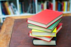 Hög av kulöra böcker på träskrivbordet Royaltyfri Bild