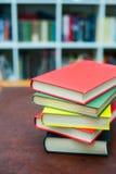 Hög av kulöra böcker på träskrivbordet Arkivbilder