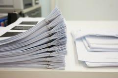 Hög av legitimationshandlingar på skrivbordet royaltyfri bild