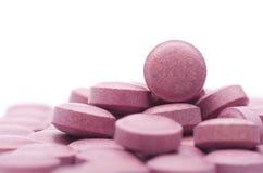 Hög av många små röda preventivpillerar, grupp av vitaminer Röda preventivpillerar på a Royaltyfri Foto