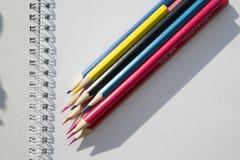 Hög av mångfärgade blyertspennor på notepadbakgrund arkivbild