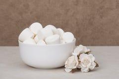 Hög av marshmallower i den vita bunken Pappers- rosor royaltyfri foto