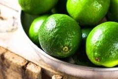 Hög av mogna färgrika limefrukter i den aluminum maträtten på den wood asken, sunlig Arkivbild