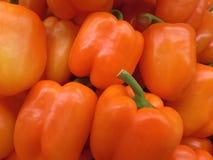 Hög av mogna ljusa orange färgspanska peppar med gröna stammar Arkivbild