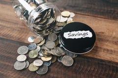 Hög av mynt i en krus med skriftliga BESPARINGAR för etikett arkivbilder