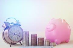 hög av mynt med klockan och piggy rosa färger Arkivbild