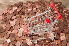 Hög av mynt och den tomma shoppingvagnen Arkivbild