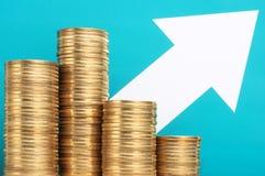 Hög av mynt och den växande pilen gör pengar växande inkomst Arkivbild