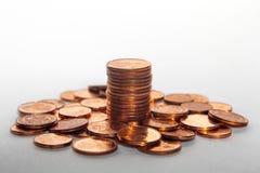 Hög av mynt och en myntbunt mellan den vit bakgrund Arkivfoto