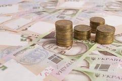 Hög av mynt och hryvnaräkningar arkivfoton