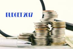 Hög av mynt och pennan och förstoringsglas med ordbudget 20 Arkivfoto