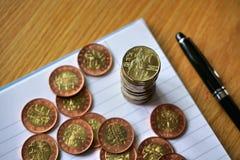 Hög av mynt på trätabellen med ett guld- tjeckiskt kronamynt i värdet av 20 CZK på överkanten Royaltyfria Foton