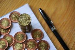 Hög av mynt på trätabellen med ett guld- tjeckiskt kronamynt i värdet av 20 CZK på överkanten Royaltyfri Foto