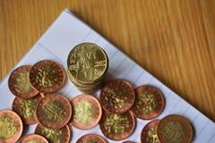 Hög av mynt på trätabellen med ett guld- tjeckiskt kronamynt i värdet av 20 CZK på överkanten Arkivfoto