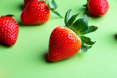 Hög av nya jordgubbar på ljust - grön bakgrund arkivfoto