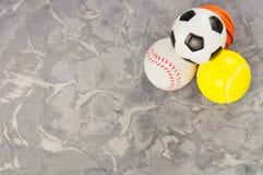 Hög av nya mjuka basket- och baseball- och tennis- och fotbollbollar för gummi fyra på gammalt slitet cement royaltyfri foto