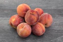 Hög av nya mogna persikor på trätabellen arkivbilder