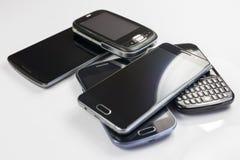 Hög av nya och gamla mobiltelefoner Arkivbild