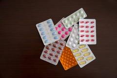 Hög av packar av preventivpillerar och kapslar som isoleras på brun träbakgrund arkivbilder