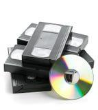 Hög av parallella videokassetter med DVD-disketten Royaltyfri Bild