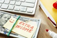 Hög av pengar med extra inkomst för tecken arkivfoton