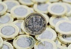 Hög av pengar och baksida av ett pundmynt Royaltyfria Foton