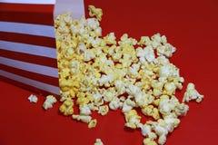 Hög av popcorn från den röd och vitbokasken på det röda golvet arkivbilder